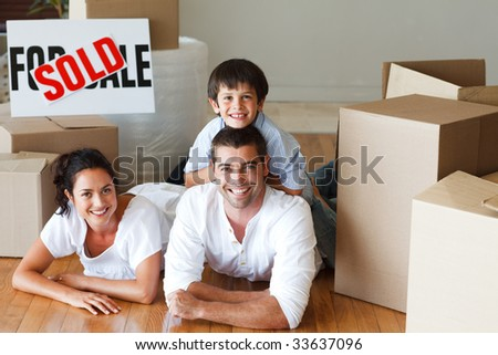 Son and parents lying on the floor of their new house smiling at the camera