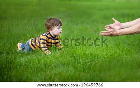 son crawling in her father's hands on green grass - stock photo