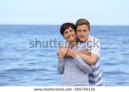 Son embraces his smiling mother on blue sea background - mature woman and boy outdoor