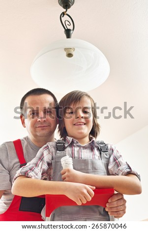Son helping father changing a lightbulb in a ceiling lamp - stock photo