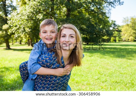 Son hugging young mother in the park
