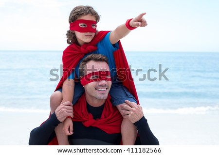 Son in superhero costume pointing while father carrying him on shoulder at beach - stock photo