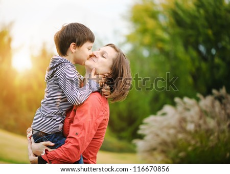 Son is kissing his mother - stock photo