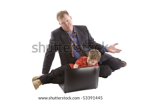 Son is working on a computer while dad looks surprised. - stock photo