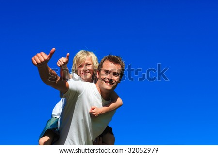 Son on father's back with thumbs up in a park - stock photo