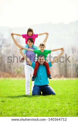 Son on father's shoulders and daughter behind on mother's shoulders outside in a colorful creative family portrait. - stock photo