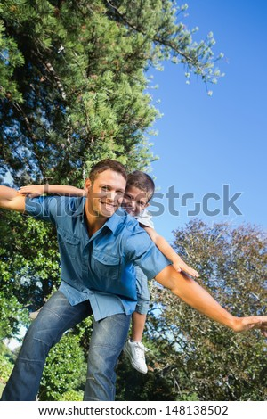 Son playing with his dad outside in the park on a summers day - stock photo