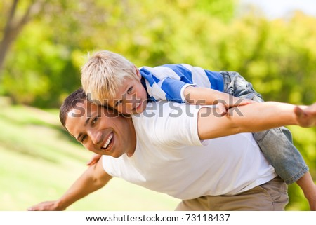 Son playing with his father in the park - stock photo