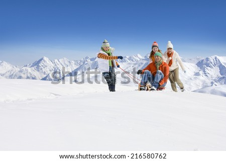 Son pulling father on sled through snow as mother and daughter push - stock photo