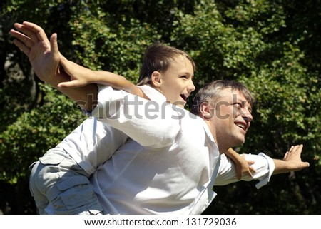 son riding on the back of his  happy dad outdoors - stock photo