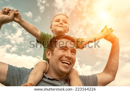 Son seating on the father under beautiful sky - stock photo