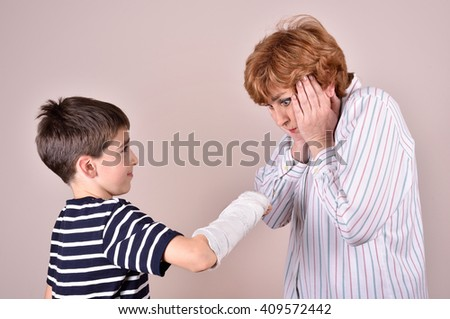 Son showing his broken arm with plaster to his mother