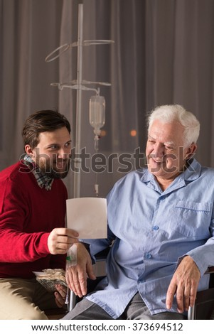 Son visiting disabled father in nursing home - stock photo