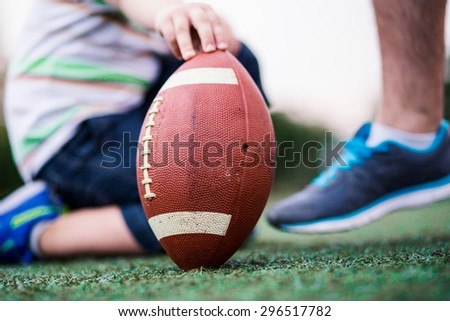 Son watching father kicking American football. Shallow depth of field - stock photo