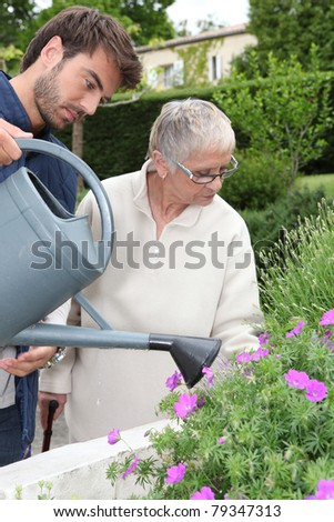 Son watering the flowers. - stock photo