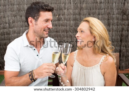 son with mother in garden drinking champagne