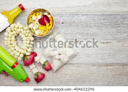 Songkran Festival : Perfume,Garland,floral,power and gun on white wooden background - stock photo