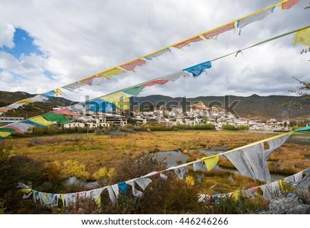 Songzanlin Monastery and the tibetan prayer flags foreground, Shangri-la County, Yunnan Province, China - stock photo