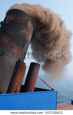 Soot and smoke billowing on the stack of a ship. - stock photo