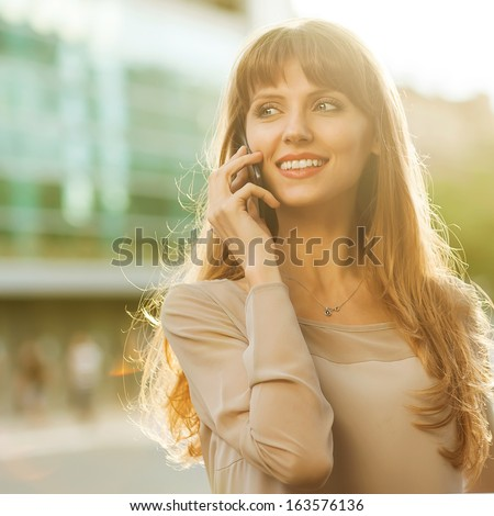 Sophisticated businesswoman in dress talking on the phone. - stock photo