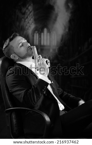 Sophisticated young man agent police killer hitman assassin sitting and resting gun on his lips over dark background black and white portrait - stock photo