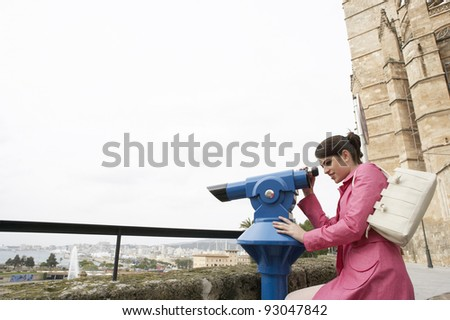Sophisticated young woman at an observatory overlooking the city. - stock photo