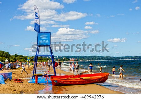 SOPOT, POLAND - AUGUST 15, 2016: Sandy beach scene of many people suntanning, relaxing and enjoying the shore in summer day in the foreground observation tower and coastguard boat.