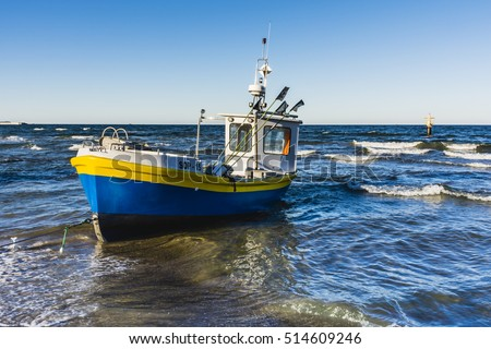Sopot, Poland - March 22, 2016: Cutter on hawser on a stormy sea. Sopot beach on the Baltic Sea.
