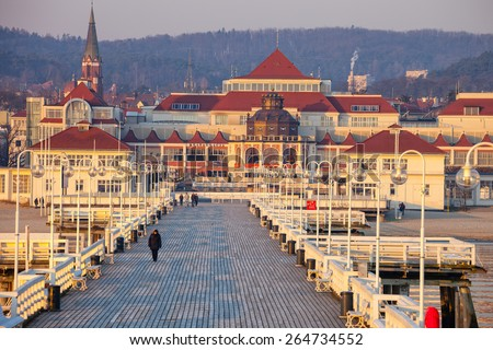 SOPOT, POLAND - MARCH 19: People walking on the Sopot Pier built in 1827. At 511m, the pier is the longest wooden pier in Europe. Pier life on March 19, 2015 in Sopot, Poland. - stock photo