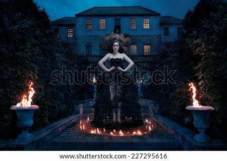 Sorceress in the middle of a ritual including fire spell - stock photo
