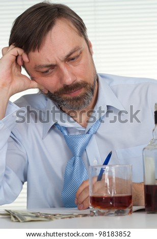 Sorrow businessman sitting at a table with a bottle on a light background - stock photo