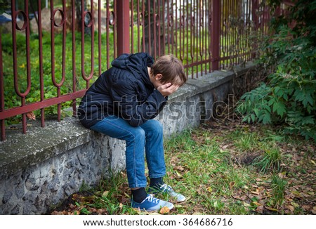 Sorrowful Kid sit on the City Street - stock photo