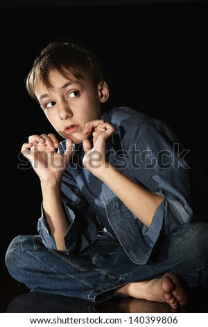 sorrowful little boy on a black background - stock photo