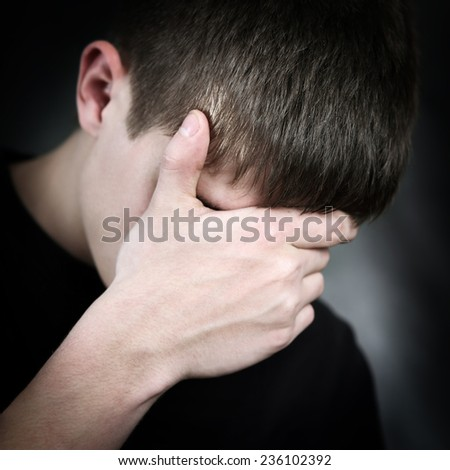 Sorrowful Young Man on the Black Background - stock photo
