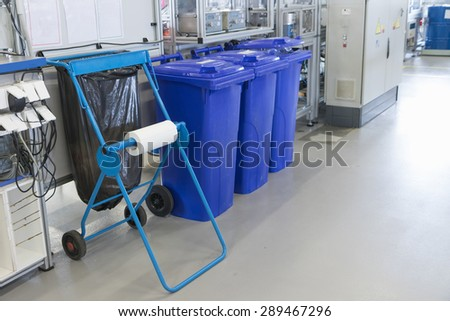 Sorting of waste into the prepared blue bins in the production hall of assembly factory. All potential trademarks are removed. - stock photo
