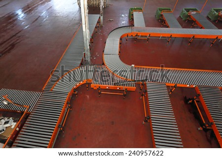 Sorting system with conveyer belt in distribution warehouse - stock photo