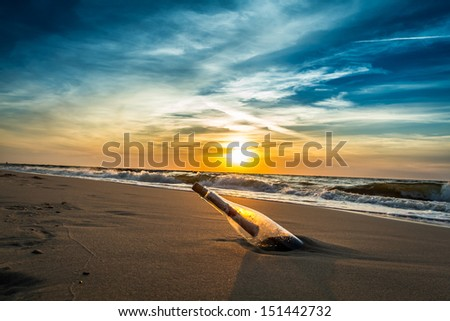 SOS message in a bottle on the beach - stock photo