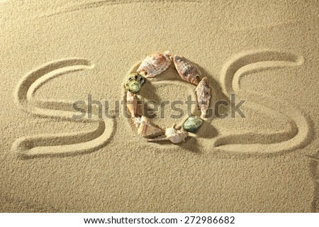 SOS words written on the sand of the beach - stock photo