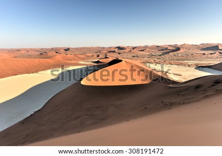 Sossusvlei (sometimes written Sossus Vlei) is a salt and clay pan surrounded by high red dunes, located in the southern part of the Namib Desert, in the Namib-Naukluft National Park of Namibia. - stock photo
