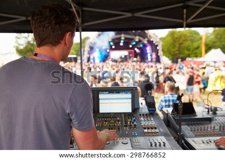 Sound and lighting engineer at an outdoor festival concert - stock photo