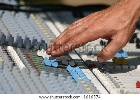 Sound engineer at mixing desk, daylight concert shot - stock photo