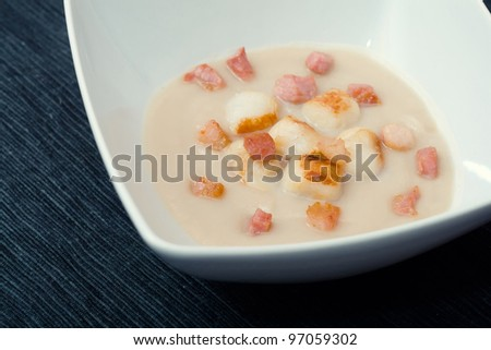Soup of Jerusalem artichokes and scallops on a dark background made with italian traditional recipe - stock photo