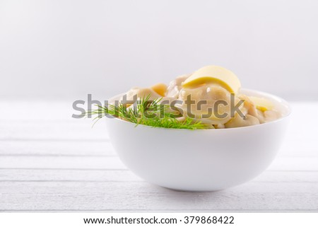 soup plate with cooked dumplings on a white wooden table - stock photo