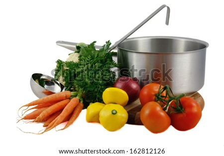 Soup vegetables including carrots, cauliflower, onion, squash, carrots with silver cooking pot and ladle isolated on white