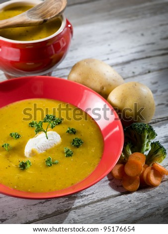 soup with carrots, broccoli, potato and sheep cheese - stock photo