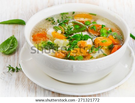 Soup  with chicken and  vegetables on a wooden table . Selective focus - stock photo