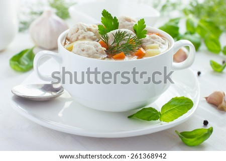 Soup with chicken meatballs and vegetables on white wooden background - stock photo