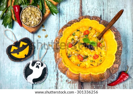 Soup with lentil in the carved pumpkin, ghost and laughing black lantern toys on the blue wooden background at Halloween party - stock photo