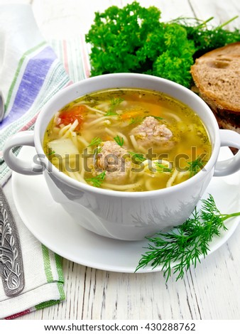 Soup with meatballs, noodles and vegetables in a white bowl and saucer, dill, bread, napkin and spoon on wooden boards background