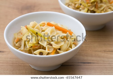 Soup with noodles and vegetables like carrots, field garlic, sprouts and noodles.
